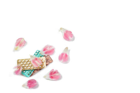 Oral contraceptive pills. Birth control pills.Contraceptive Pill and Flowers Rose petals on white Background.