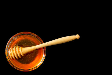 Honey in bowl with wood stick isolated on black background