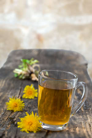 Dandelion tea background, herbal remedy. Dandelion tea, flower, leaves and root on wooden background.