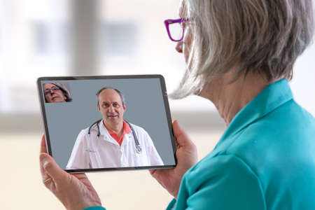Telemedicine concept, Doctor sitting at hospital, with laptop, having an online call with a patient showing a ablet device