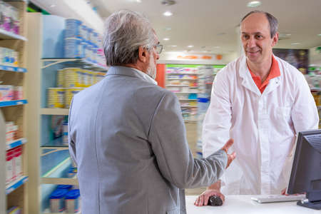 middle aged pharmacist and senior customer discussing medications inpharmacy