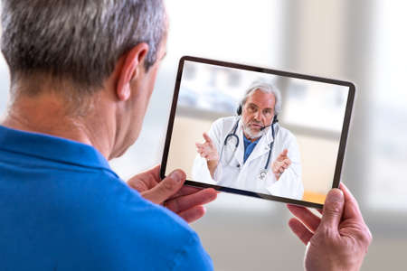 Concetto di telemedicina, dottore seduto in ospedale, con laptop, con una chiamata online con un paziente che mostra un dispositivo abilitato Archivio Fotografico