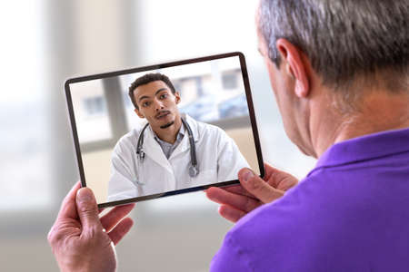 Telemedicine concept, Doctor sitting at hospital, with laptop, having an online call with a patient showing a ablet device Stock Photo