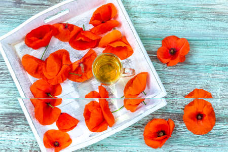 Red poppy flower tea drink in glass mug on wooden background. Concept of healthy eating.