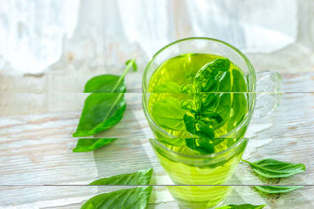 Herbal medicine : Calming tea in a tea cup with basil leaves on a kitchen table Imagens
