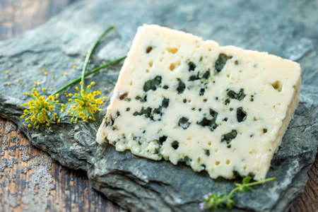 French blue cheese Roquefort, made from sheep milk in caves of Roquefort-sur-Soulzonwith grapes on grey stone Imagens