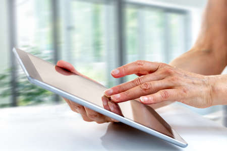 Communication technology concept. Woman hand holding tablet smart device with typing message or checking newsfeed on social networks, Stock fotó