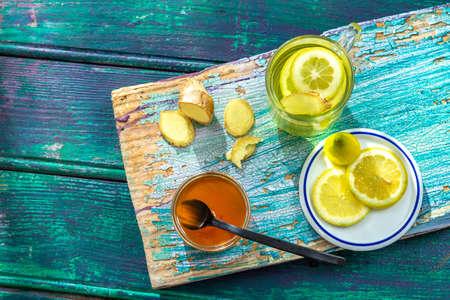 Hot ginger lemon tea. Healthy, on old green board againt green wooden background Imagens