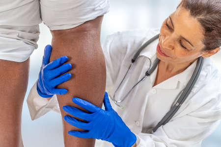 phlebologist inspecting a womans leg looking for varicose veins on white background