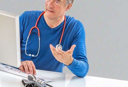 Online medical consultation: Doctor expplaining diagnosis while sitting in hfront computer with patient