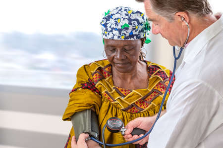 Arzt im weißen Mantel, der den Blutdruck einer anfivan olf Frau im Krankenhaus misst