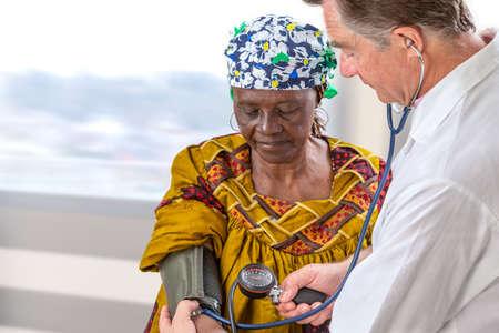 dottore in camice bianco che misura la pressione sanguigna di anfivan olf donna in ospedale