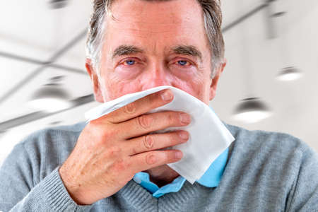 Senior Man with a common cold is blowing his nose with a tissue