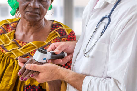 Elderly woman getting check-up at dermatologist.,usig magnifying glass to see mole