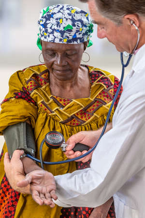 doctor in wite coat measuring blood pressure of anfivan olf woman in hospital