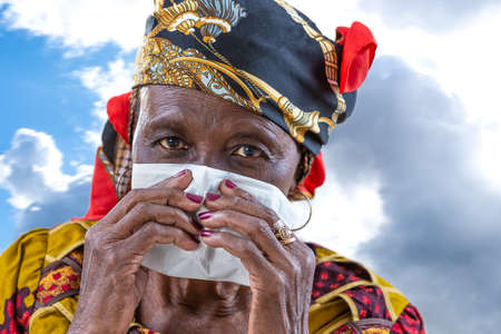 Senior afrcan woman with a common cold blowing his nose with a tissue