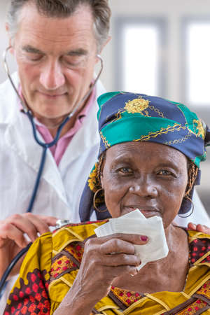 Stethoscope examination. General practice doctor listening to a 70-year-old African womans back. with stethoscope used to listen the heart and lungs, in order to diagnose various disorders.