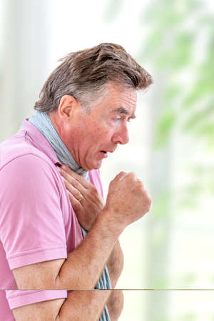 A mature gentleman coughing because of pulmonary disease isolated on white background Stok Fotoğraf