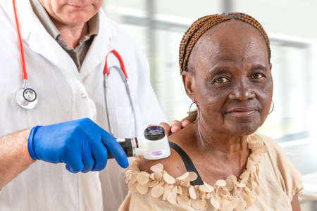 Elderly woman getting check-up at dermatologist.,usig magnifying glass