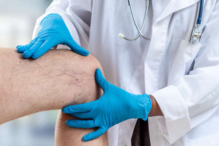 Close-up image of female doctor cheking knee of male patient