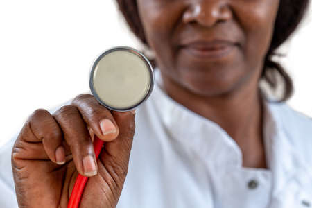 Close-up of an african, American, doctor s hand holding a stethoscope outstretched towards the viewer. Healthy lifestyle concept