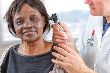 Doctor holding otoscope and examining ear of senior African woman.