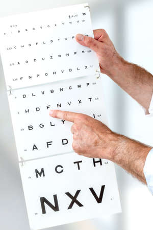 Ophthalmologist checking patient eyesight, pointing letters, eyes examination at office