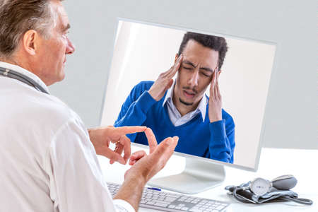 doctor with n front of her laptop during a video call with a fibromyalgia patient having sleeping trouble, headaches, depression Stock Photo