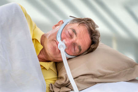 Man wearinhg a maslk Sleep Apnea and CPAP. Prescription, to sleep for safe life