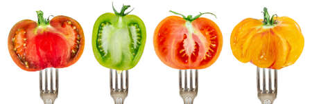 Collection of half tomatoes on forks aligned and isolated on white