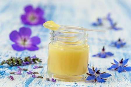 Raw organic royal jelly in a small bottle with litte spoon on small bottle surrounded by flowers. 版權商用圖片