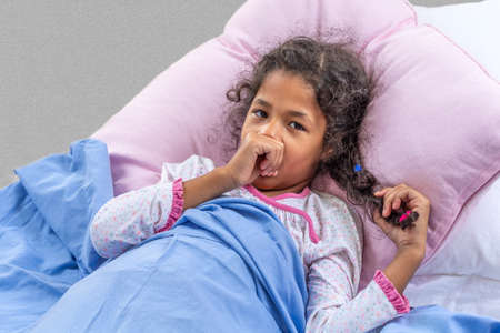 Close portrate cute multiracial girl of 6-10 years old who is sucking her thumb in the bed Stockfoto