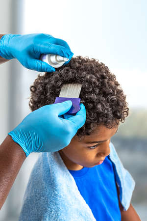 Doctor Looking for lice on childs head.
