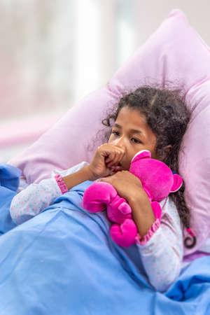 Close portrate schattig multiraciaal meisje van 6-10 jaar oud die zijn duim in het bed zuigt met roze teddy