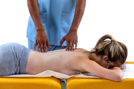 Close up of physiotherapist manipulating body part on young woman. Girl laying on madical bed