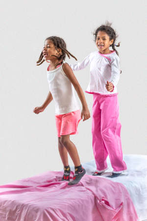 Two little girls jumping in the bed. pink color code Stockfoto - 134285288