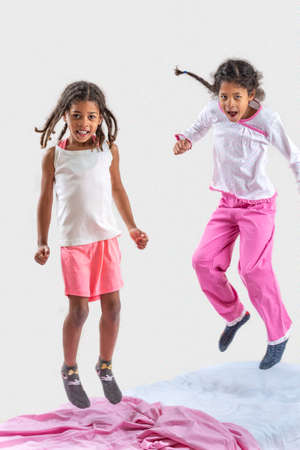 Two little girls jumping in the bed. pink color code