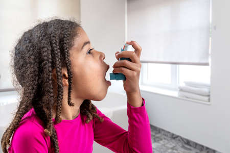Close-up portrait of cute 5 year old girl using his asthma inhaler, profile view white background Foto de archivo