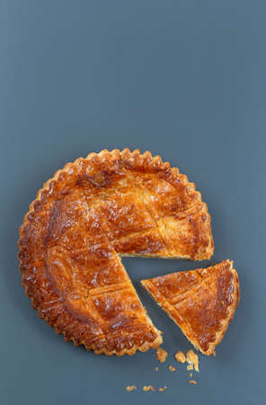 Homemade Twelfth Night cake (french galette des rois) made of puff pastry, slice apart with the charm inside,