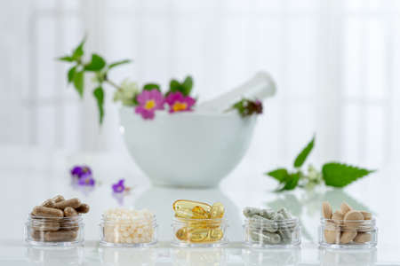 Bottle of pills food suplements healthy medicine medication health care treatment additives pharmacy with ceramic white portar with medicinal fresh plants on background