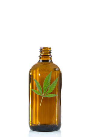 Cannabis essential oil, CBD oil extract with canabis sativa green leaf Marihuana isolated on white background. Medical marijuana , herbal medicine plant and health care concept. Space for text. Stock Photo