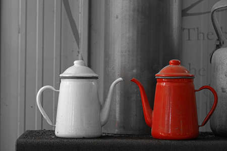a white kettle and a red kettle