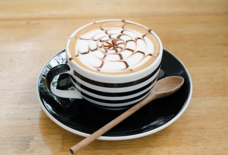 A cup of coffee on wooden background, latte art photo