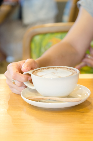 Cup of coffee and woman hand photo