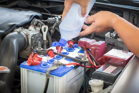 distilled water: car battery maintenace with distilled water Stock Photo