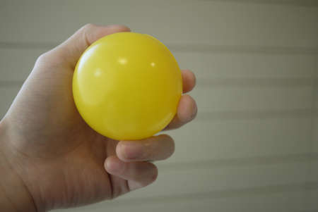 yellow plastic ball on hand