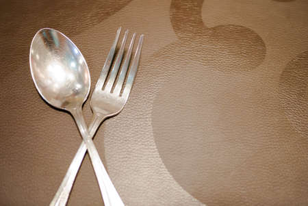 fork and knife placed on brown texture  able to use as background Stock Photo - 17307471