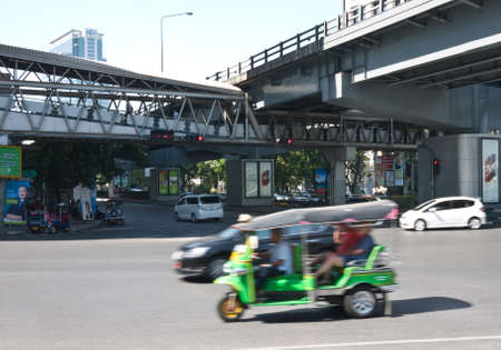 mototaxi: Bangkok, Thailand, January 18, 2013 - Tuk-tuk with foreign passenger driving in business area of bangkok
