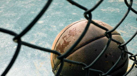 the old aged leather basketball showing its texture behind the wire fence