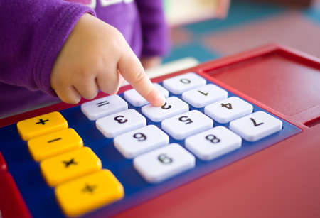 kids finger pressing toy calculator Stock Photo